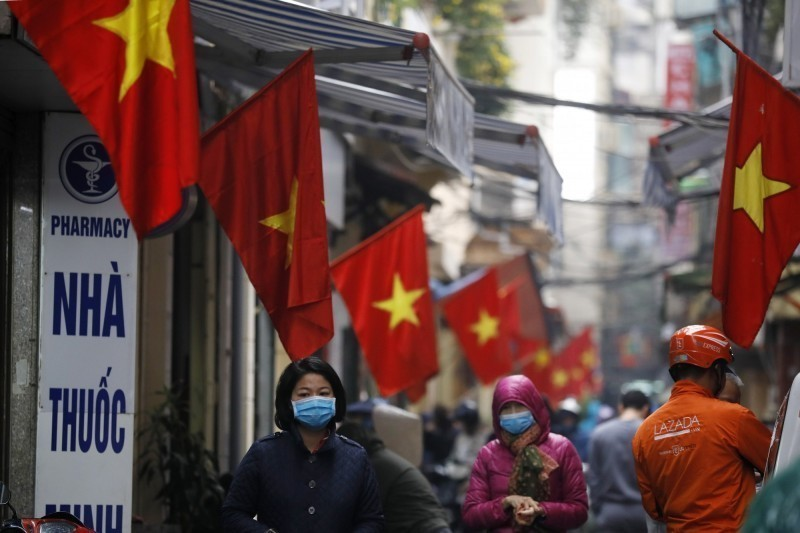 越南出現首名死亡病例,是來自廣南省(Quang-Nam)的70歲男性,在峴港測試呈陽性。圖為越南民眾戴口罩防疫。(歐新社)