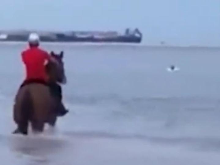 中國福建有個男孩在海灘玩水,被海浪捲走,在沙灘上騎馬的3名男子直接騎著馬衝下水,成功救回男孩。(圖擷自微博)