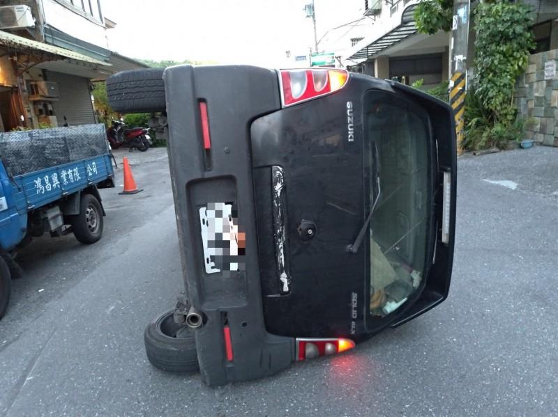 李姓男子駕車自撞路旁的二部小客車,整台車側翻後橫躺路中央。(記者王錦義翻攝)