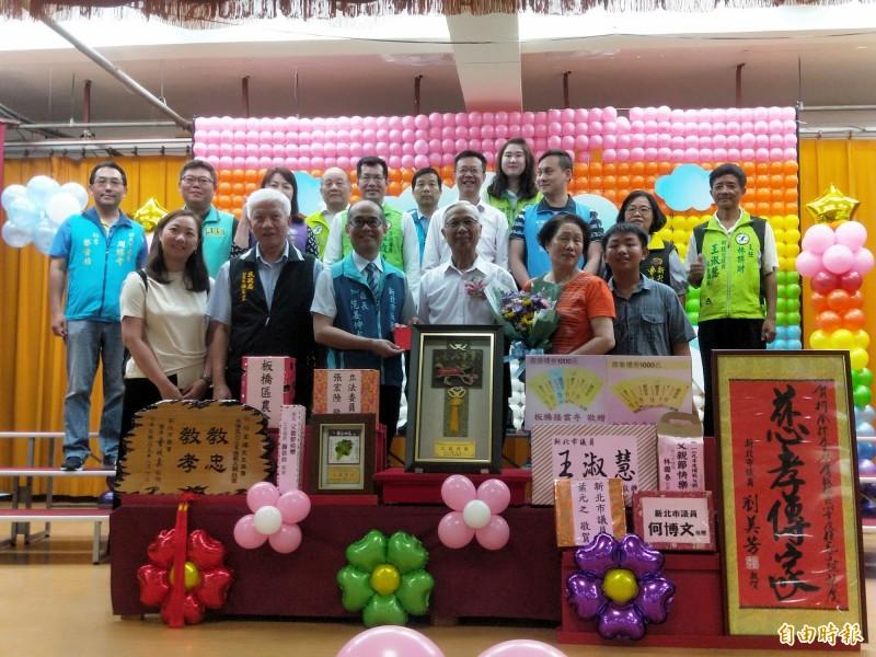 板橋區公所表揚投身社區服務不遺餘力的模範父親彭朝炫(前排右3)。(記者何玉華攝)