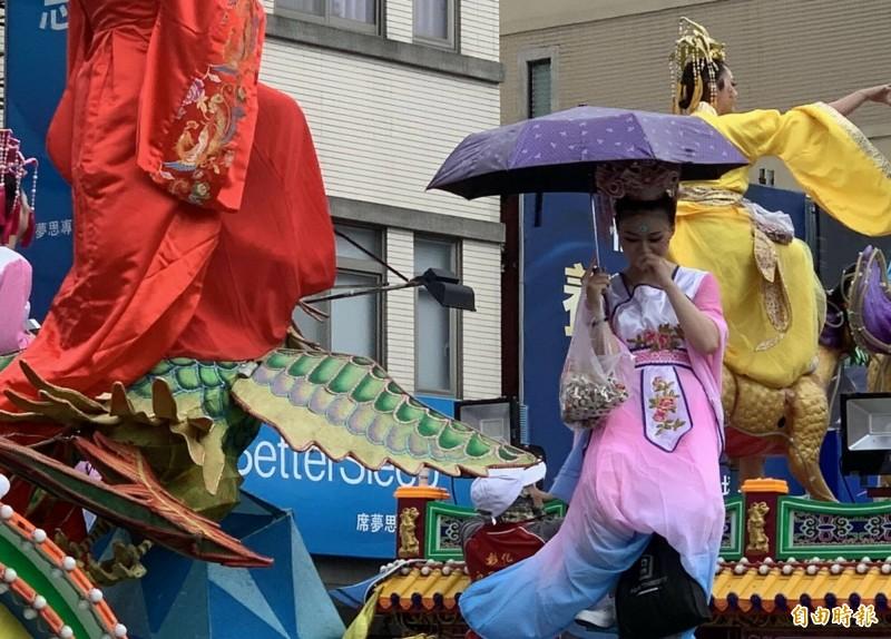 城隍爺出巡彰化市遶境,花車仙女紛紛撐傘遮陽,信眾笑稱:「凡間太熱了,連仙女也怕中暑!」(記者湯世名攝)