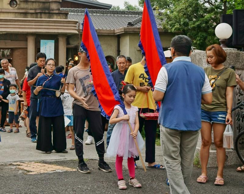 小朋友們舉著客家傳統彩旗、拿著祭品前往花樹下伯公祭拜。(記者許麗娟翻攝)