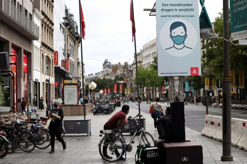 圖為比利時安特衛普一景。圖上標語寫著:每個人都需要戴上口罩。(路透)