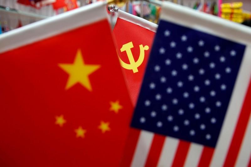 美國史丹佛大學胡佛研究所日前發布一項新報告指出,美國與中國學者及研究機構合作直接促進中國「軍事現代化」,等同於「幫中國擦槍」。圖為美國國旗、中國國旗和中共黨旗。(路透)