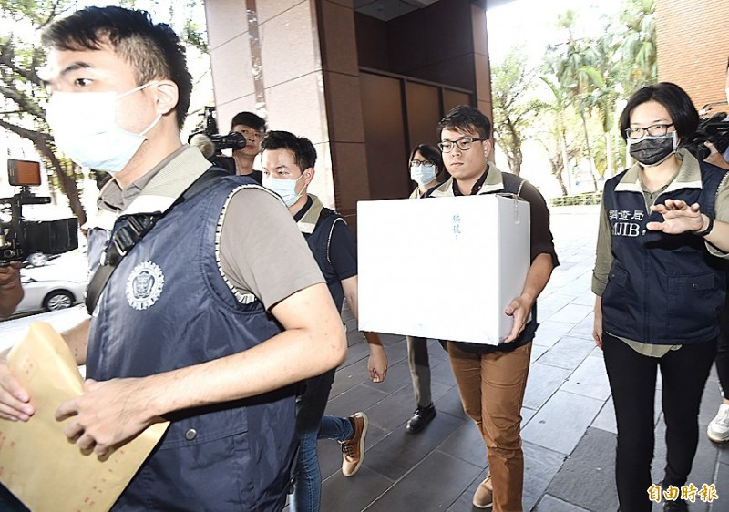 Ministry of Justice Investigation Bureau staff carry boxes with documents gathered in connection to a corruption probe involving several legislators in Taipei yesterday.   Photo: Chien Jung-fong, Taipei Times