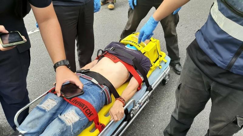 消防員將摔斷腿的潘男送醫。(記者徐聖倫翻攝)