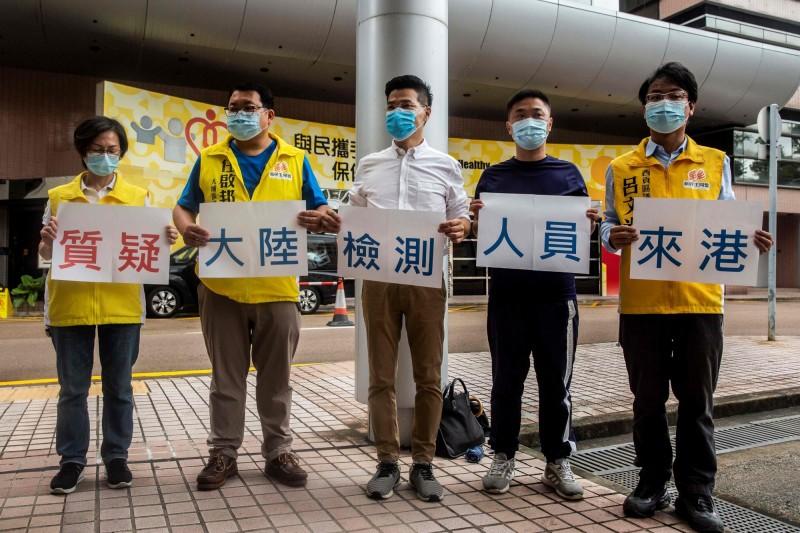 香港「新民主同盟」成員抗議北京派檢測員來港,並擔心港人 DNA樣本被「送中」。(法新社)