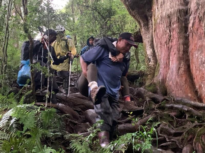 張小姐在宜蘭縣加羅湖山區登山時腳部受傷,消防員以人力接駁方式背下山。(記者江志雄翻攝)