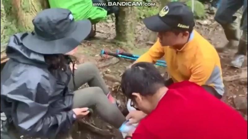 消防員幫張小姐(左)左腳包紮固定後再背下山。(記者江志雄翻攝)