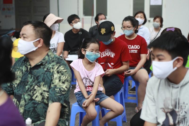 圖為河內民眾在醫院外等待接受武漢肺炎篩檢。(美聯社)