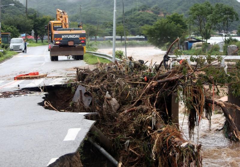 忠州一大早有80多所房屋被洪水淹沒,迫使約120名居民於清晨撤離。圖為忠州道路地基被大雨掏空。(歐新社)