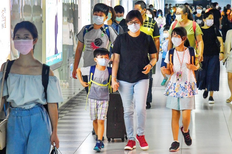People wear masks as they walk through the Taipei City Mall under the Taipei Railway Station yesterday.  Photo: CNA