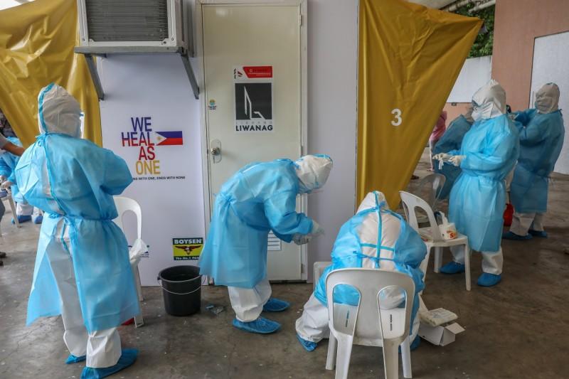 菲律賓的武漢肺炎確診病例今(2)日突破10萬大關。圖為醫務人員在奎松市為採檢準備工具。(歐新社)