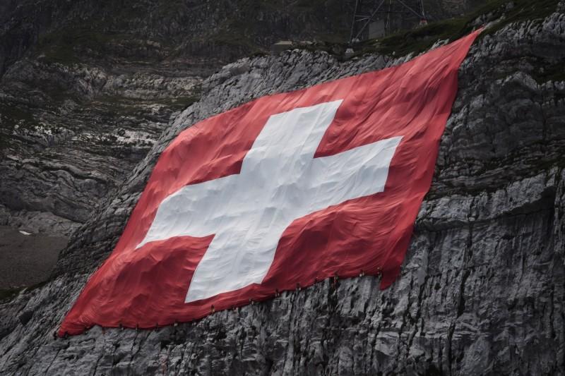 週六(1日)為瑞士國慶,瑞士國民在封鎖政策下低調慶祝國慶日。圖為登山者為慶祝國慶在瑞士森蒂斯山(Saentis)上懸掛的大型瑞士國旗。(法新社)