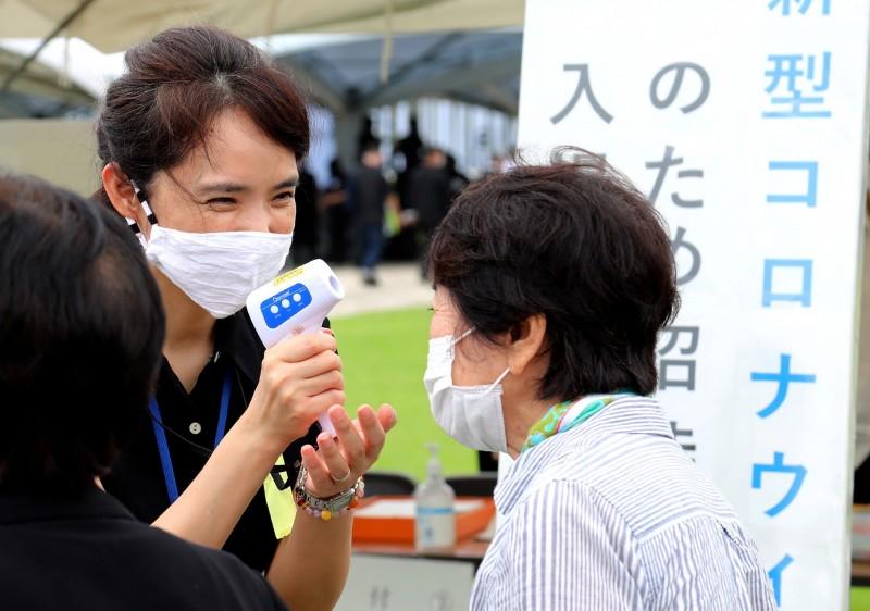 根據《NHK》整理數據指出,若依一週每10萬人的確診人數來分析,沖繩縣約18.38人確診,是全日本最高,其次是東京都的15.72人。圖為沖繩防疫人員為民眾量體溫。(歐新社)