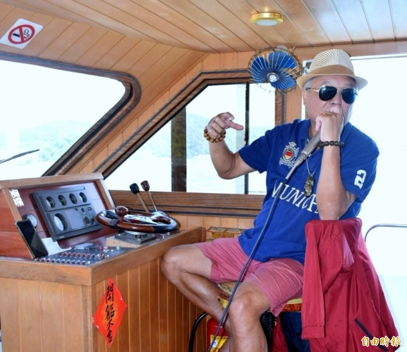 前日月潭遊艇公會理事長莊武源一邊開船、一邊解說總統魚的故事。(記者謝介裕攝)