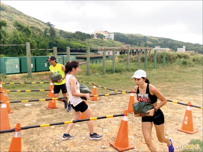 連江縣「東引軍事越野障礙賽」16公里菁英競賽組昨天登場,圖為雷里莎(右)抱著沙包跑障礙。(記者俞肇福攝)