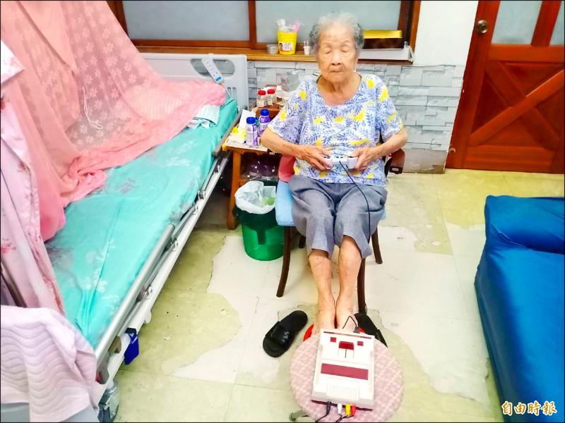 98歲的魏金花阿嬤喜歡打紅白機電玩維持頭腦清醒,20年來已玩壞3台主機、10多支遙控器。(記者陳冠備攝)