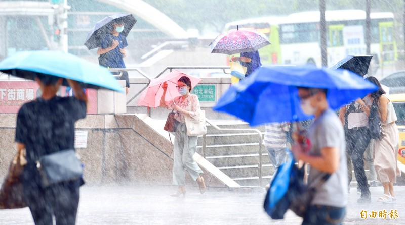 People walk through a rainstorm in Taipei yesterday as Typhoon Hagupit moves away from the northwest coast of Taiwan.   Photo: Peter Lo, Taipei Times