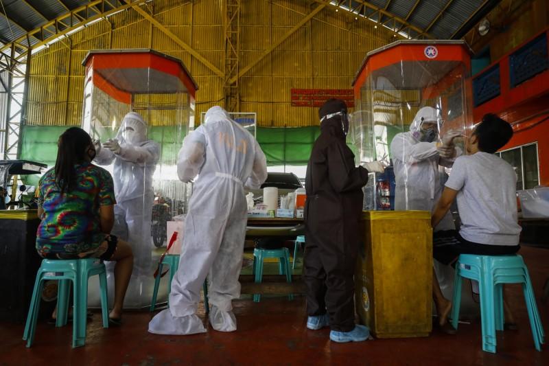 菲律賓疫情惡化,總統杜特蒂2日晚間宣布的新的封城措施,適用於首都馬尼拉與馬尼拉周邊的呂宋島4個省分。圖為馬尼拉都會區的護理人員為民眾採檢。(歐新社)