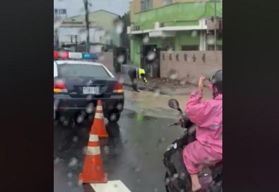有網友在臉書上分享,警察為了疏通局部淹水,徒手挖開堵塞在水溝蓋的落葉,影片曝光讓不少網友大讚。(圖取自爆廢公社)