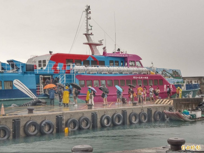 哈格比遠離、海象回穩,不少旅客冒雨搭船繼續未完旅程。(記者陳賢義攝)