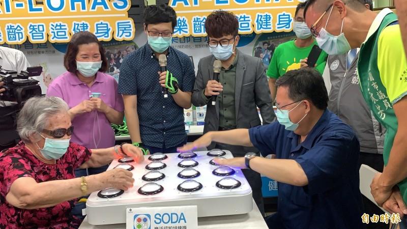 市長鄭文燦(右)坐下和95歲阿嬤在類似打地鼠的按燈遊戲「SODA─手眼協調」中對戰,最後由阿嬤獲勝。(記者陳恩惠攝)