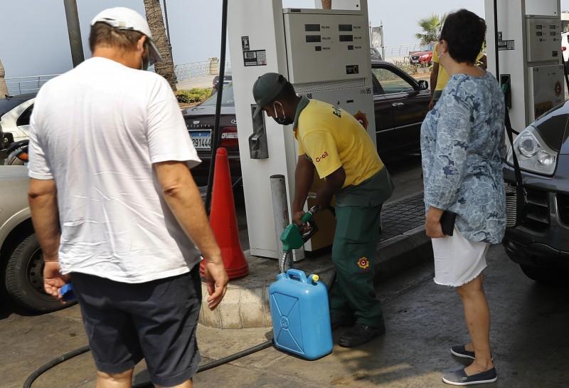 黎巴嫩人提著桶子到加油站裝滿汽油,因為每日的供電時間只有4小時左右,其餘時間必須使用家用發電機,但全國的加油站也紛紛關閉。(美聯社)