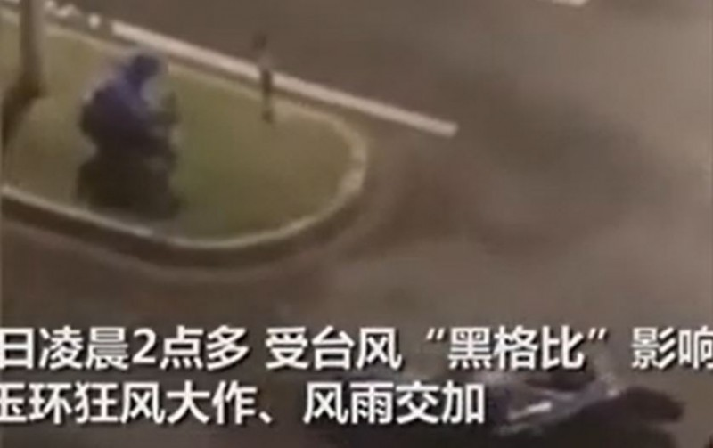 今日凌晨2點多,浙江有位外送員不畏風雨出發外送,他不敵強勁的風雨,整個人緊抱路旁的桿子,而他的電動車則倒在附近。(圖擷自Passion News YouTube)