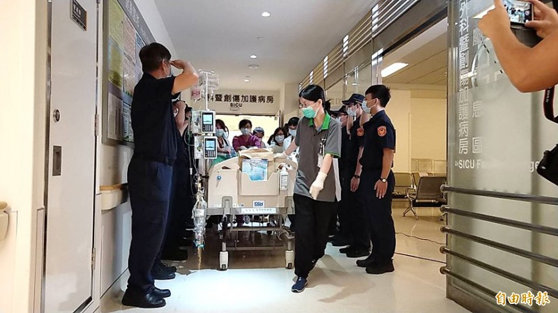 Police officers from New Taipei City's Shulin Precinct line a hallway at Far Eastern Memorial Hospital in Banciao District yesterday to salute the body of colleague Yang Ting-hao as it is transported for organ donation. Photo: Lai Hsiao-tung, Taipei Times