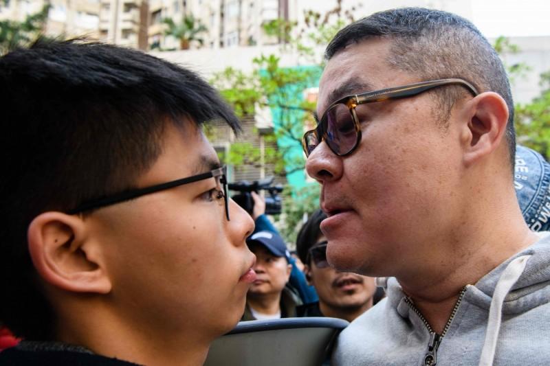 黃之鋒(左)與香港建制派支持者(右)對峙。(法新社)
