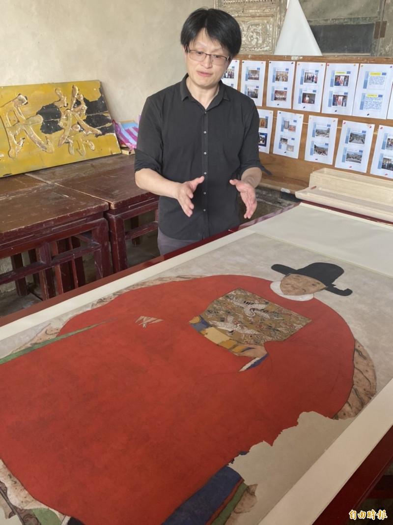 「蔡復一畫像」修護師范定甫指著修復後的複製品說,光是修復蔡復一畫像原來被覆蓋的PU塗漆,就花了半年多時間。(記者吳正庭攝)