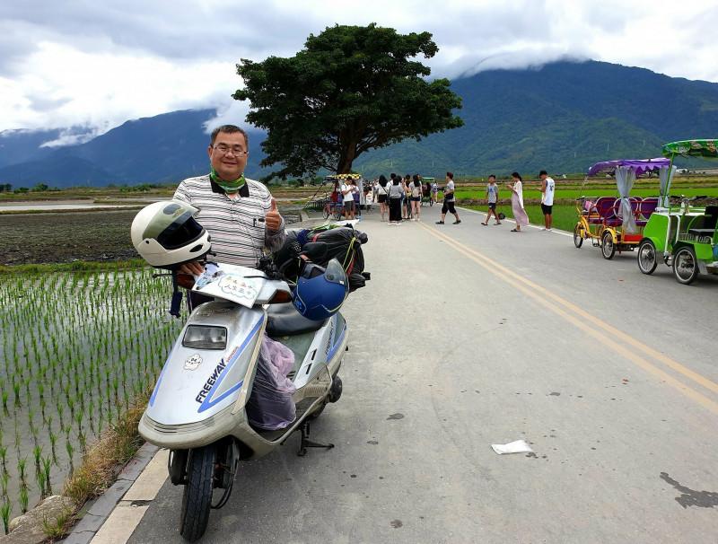 黃仲平騎著30年歷史的豪邁機車環島,來到台東與知名「金城武樹」合影。(黃仲平提供)