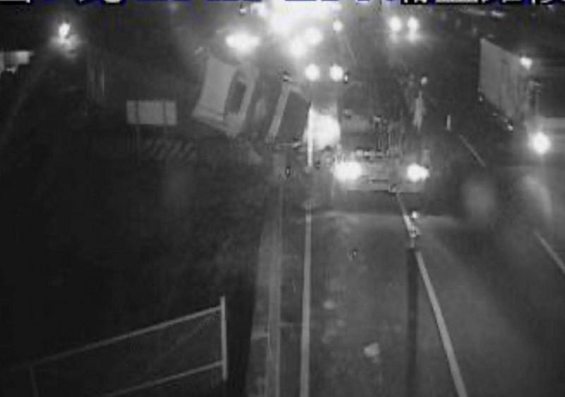 國道1號彰化秀水路段今晚驚傳貨櫃車翻覆,貨櫃車翻覆在外側車道與邊坡草皮區。(翻攝國道即時影像)