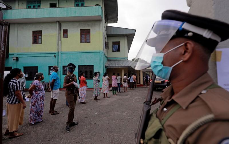 斯里蘭卡在疫情下舉行國會大選,選務人員戴著透明面罩,民眾則戴著口罩排隊投票。(路透)