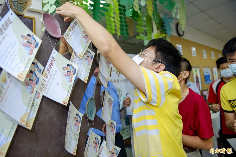 美善智青在感恩卡上寫下感謝話語,並將卡片掛上由智青手作的陶藝樹上,感謝大家成就與支持美善的服務。(記者蔡文居攝)