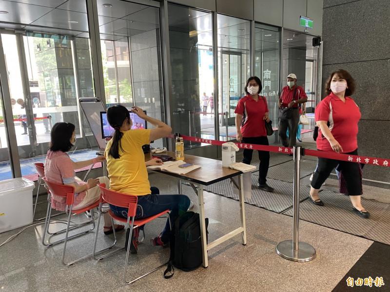 進入新北市政府大樓實施量測體溫,目前鼓勵進出人員戴口罩。(記者賴筱桐攝)