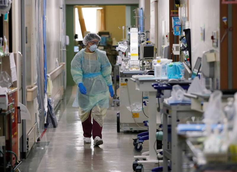 日本5日全境新增1357例確診病例,連續第2日維持千例以上。圖為東京一間醫院醫護人員工作情況。(路透)