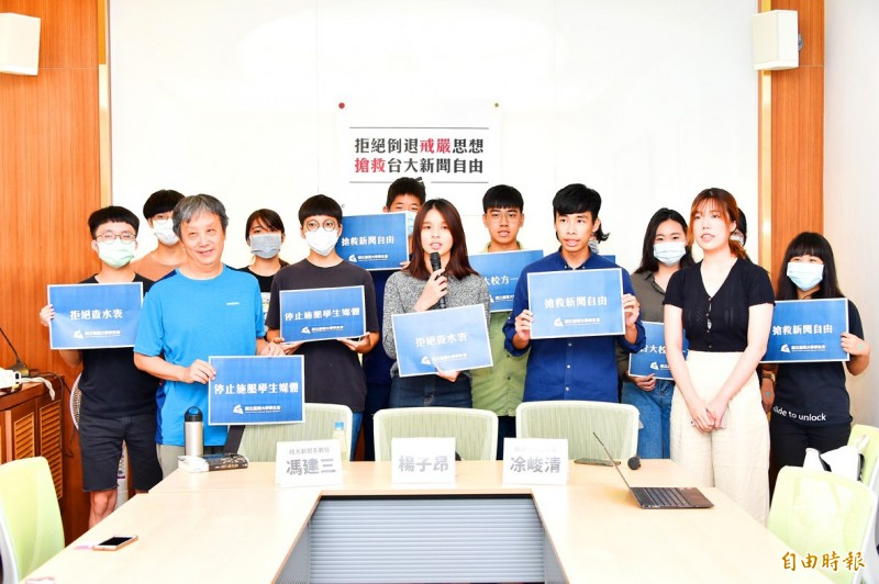 Members of the National Taiwan University Students' Association hold signs at a news conference in Taipei yesterday. Photo: Tu Chien-jung, Taipei Times