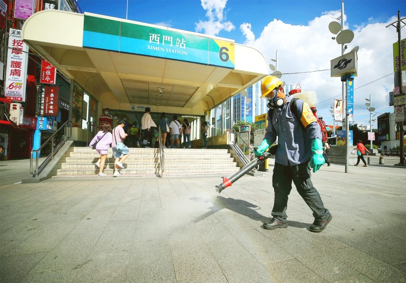 A Taipei Department of Environmental Protection employee sprays sanitizer outside an exit of the Ximen MRT station in Taipei yesterday. Photo: CNA