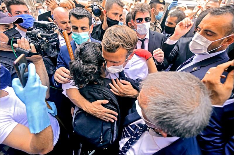 法國總統馬克宏6日至黎巴嫩首都貝魯特慰問,在受到爆炸重創的一處社區擁抱一名黎巴嫩女孩。(法新社)