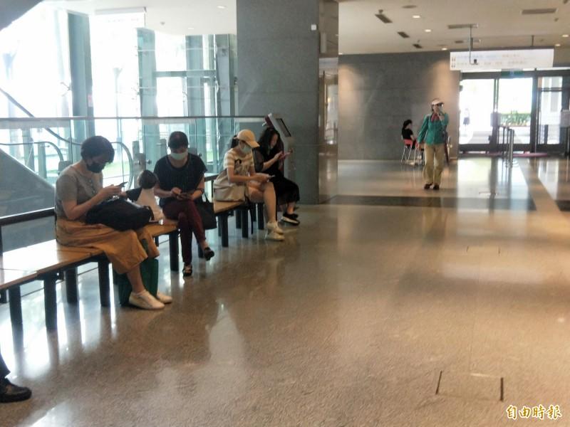 進出新北市政府大樓洽公的民眾,多數已自主戴起口罩。(記者何玉華攝)