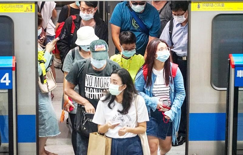 Passengers wearing masks exit a Taipei MRT train yesterday. Photo: CNA