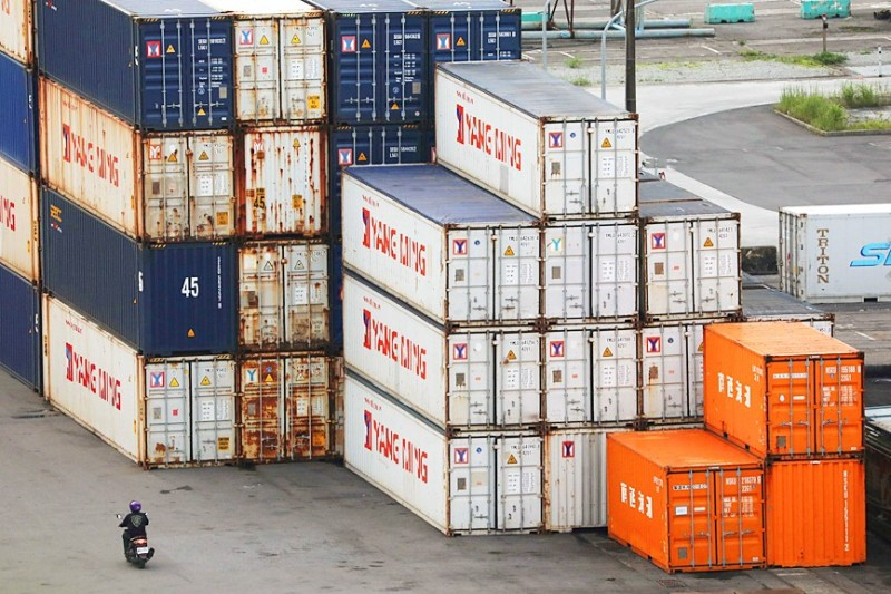 A scooter rider passes shipping containers at the Port of Keelung on June 10. Photo: Ann Wang, Reuters
