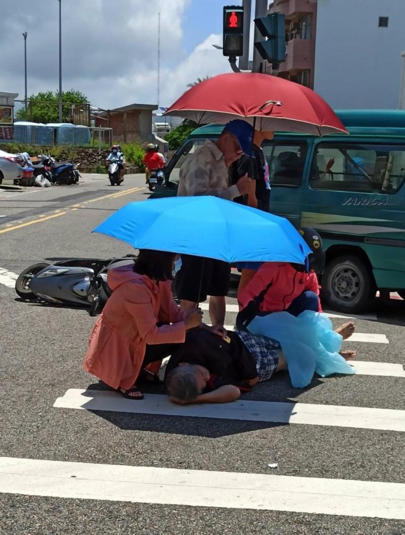 鄰近住家及路過民眾,紛紛拿出陽傘與雨衣為傷者遮陽。(陳永富提供)