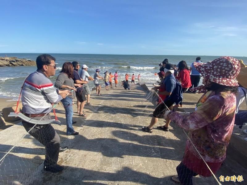 金門縣成功休閒漁業發展協會舉辦「88節親子牽罟樂」,大家合力在岸上「與大海拔河」。(記者吳正庭攝)