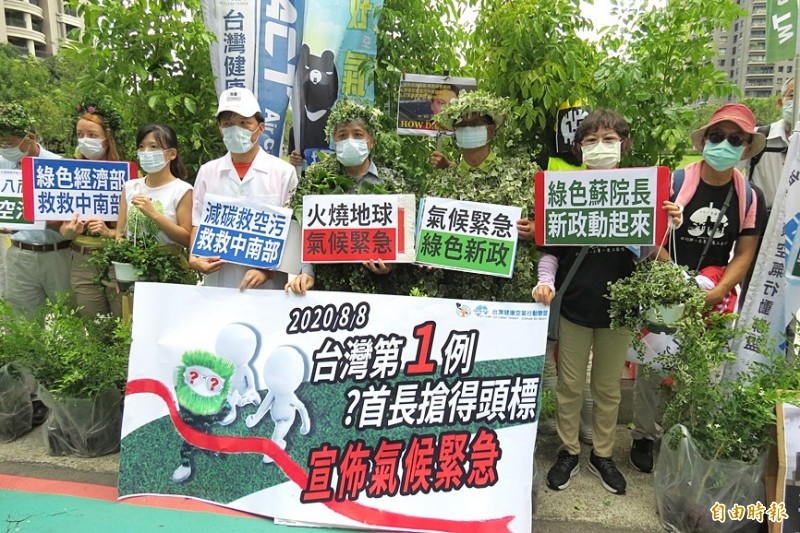 Members of environmental and healthcare groups hold signs with pro-environmental slogans at a news conference in Taichung yesterday before a parade calling on the government to cut air pollution and coal use. Photo: Su Chin-feng, Taipei Times