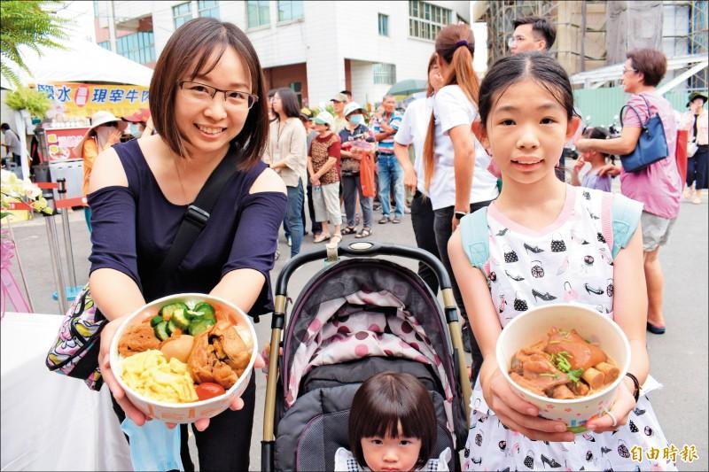 鹽水農會百歲慶生,遊客拿到社區風味餐和豬腳麵線試吃。(記者楊金城攝)