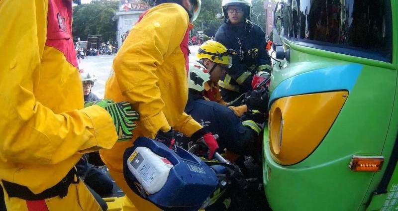 消防救護人員利用氣動式頂舉袋及電動油壓剪等救助器材,將公車底盤撐起,才讓女騎士順利脫困。(嘉市消防局提供)