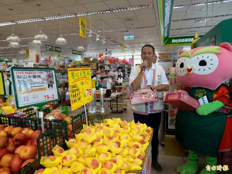 和平區代理區長古志偉(左)及梨山觀光大使「樂桃桃」帶著梨山水蜜桃,到超市擔任一日店長促銷。(記者張菁雅攝)